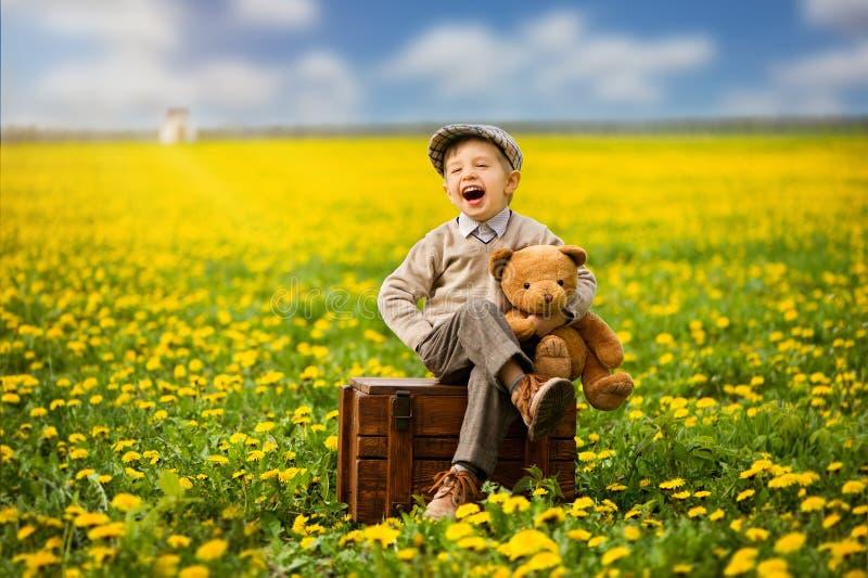 Симпатичный, усмехаясь мальчик сидя на коробке с плюшевым медвежонком на весеннем времени Карее дерево стоковое изображение rf