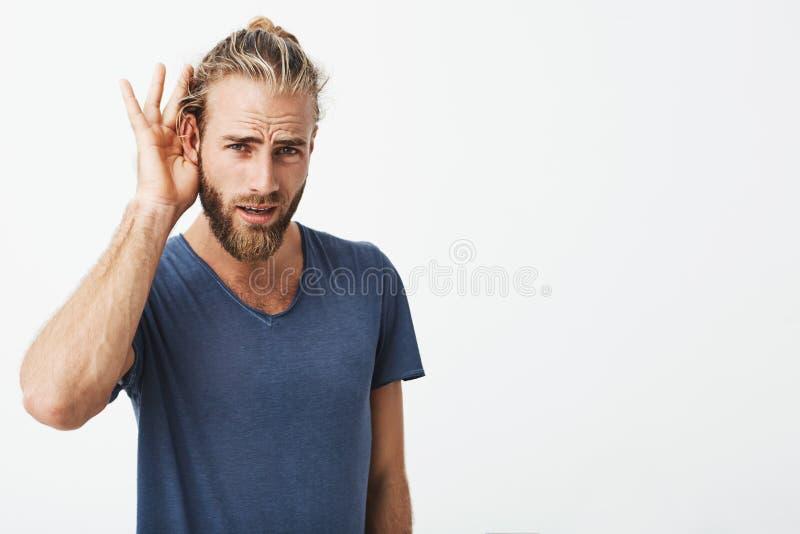 Симпатичный шведский парень с бородой и холодный стиль причёсок держа руку около показа уха он надевает ` t слышит последние слов стоковая фотография
