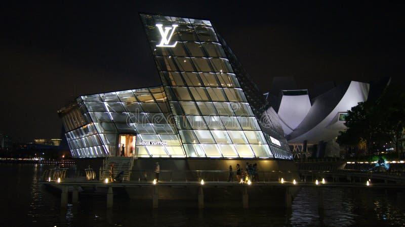 СИНГАПУР - 2-ое апреля 2015: Сцена ночи острова Maison Louis Vuitton на заливе Марины стоковые фото