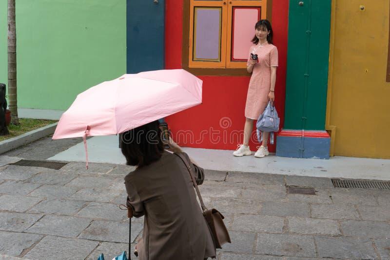 Сингапур, Сингапур - 1-ое мая 2019 - 2 неопознанных женщины принимает фото во фронте на доме Tan Teng Niah бывшем на 1,2019 -го м стоковое фото
