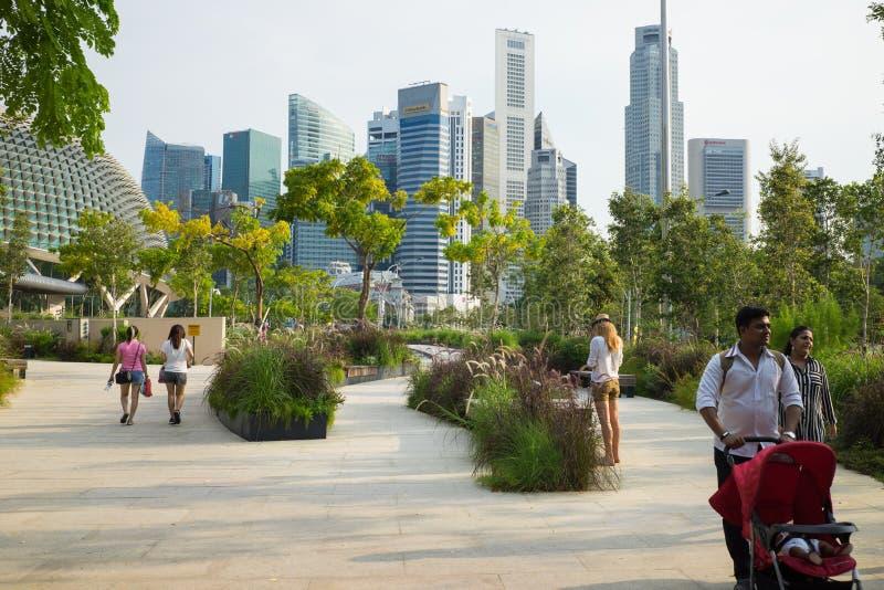 Сингапур - 1-ое мая 2016: Припаркуйте при люди идя для прогулки против высокого здания на предпосылке в Сингапуре стоковая фотография