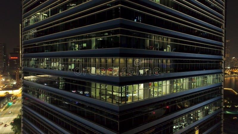 Сингапур - 25-ое сентября 2018: Закройте вверх для экстерьера современного угла офисного здания с освещенными окнами и людьми стоковая фотография
