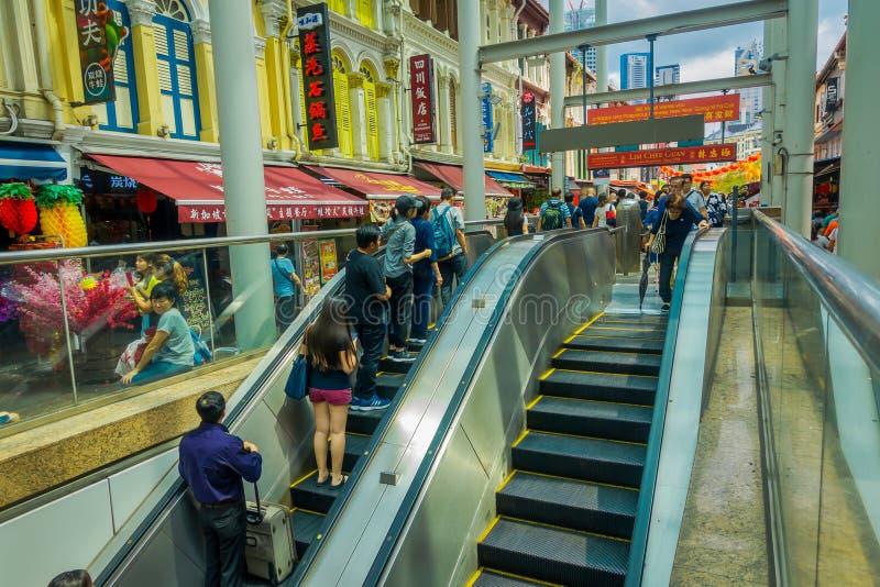 СИНГАПУР, СИНГАПУР - 30-ОЕ ЯНВАРЯ 2018: Неопознанные люди используя электрические лестницы на юлить улица Чайна-тауна стоковые изображения