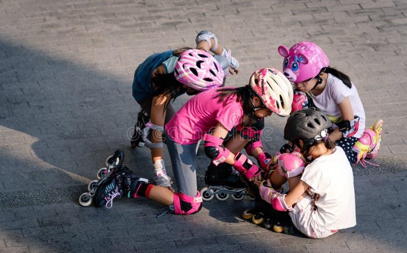 Сингапур 23-ЬЕ МАРТА 2019: девушки изучают ролик и помогают одину другого на земле стоковая фотография rf