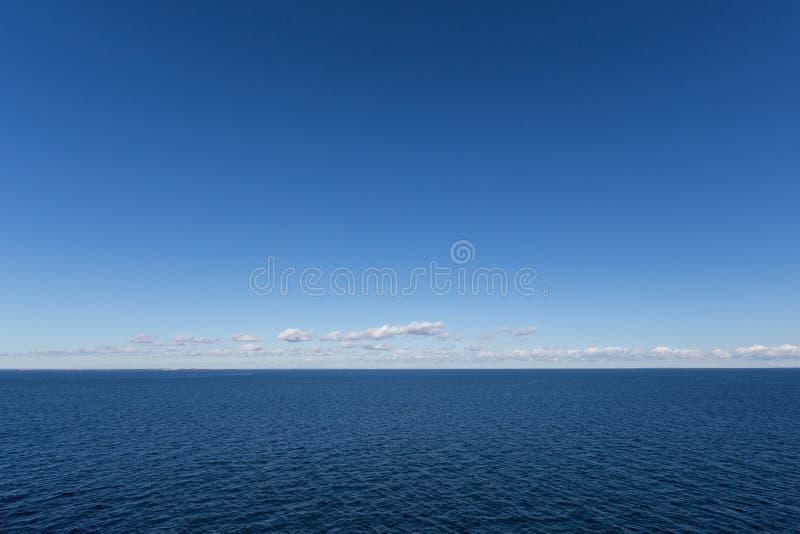 Синее северное море с голубым небом и полосками облаков над горизонтом стоковая фотография