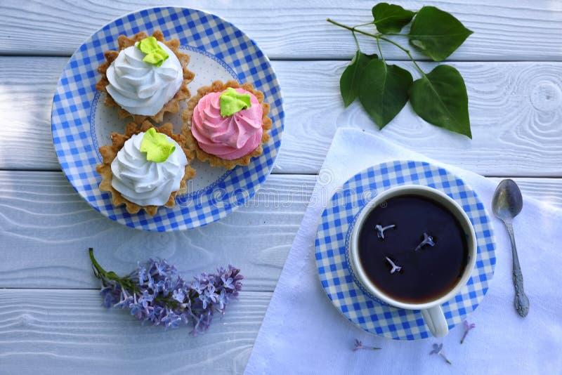 Сине-и-белая checkered чашка чаю с печеньем на белом деревянном столе стоковое фото