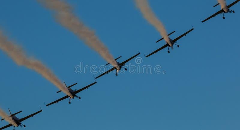Синхронизированный след дыма команды авиасалона самолета стоковые фотографии rf