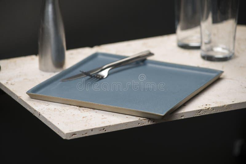 Синь, квадрат обедая плита с стеклами, нож, и вилка стоковая фотография