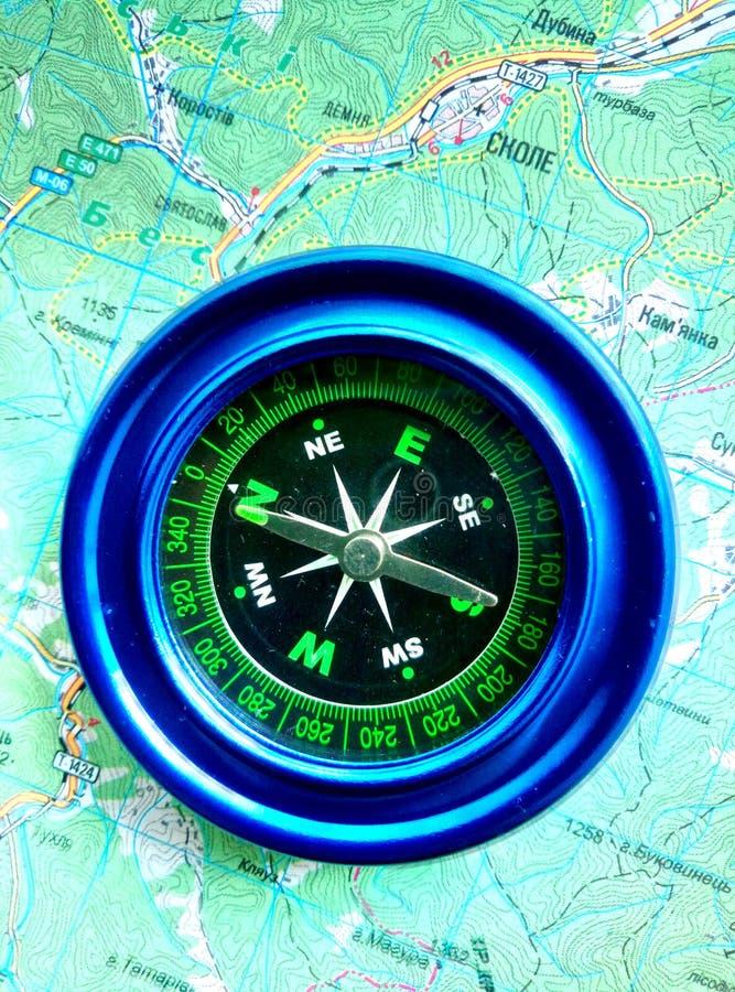 Синь магнитного компаса на дорожной карте стоковое фото