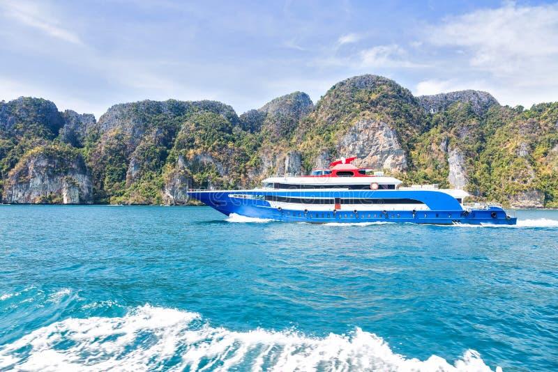Синь с белой и красной шлюпкой скорости удовольствия акцентов Плавание на море против тропического острова горы Взгляд со стороны стоковые фотографии rf