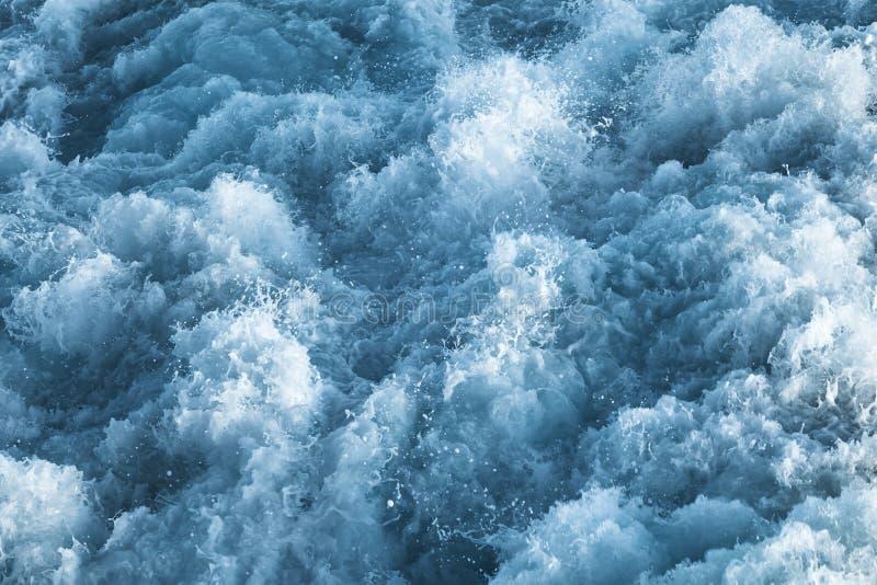 Синяя бурная вода океана с брызгает стоковое изображение