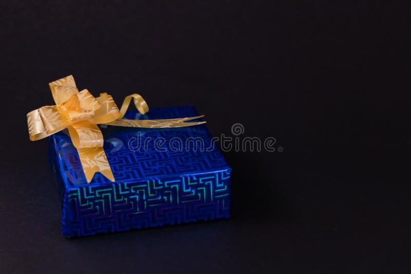Синяя подарочная коробка с золотой лентой, изолированная на темном фоне стоковые фотографии rf