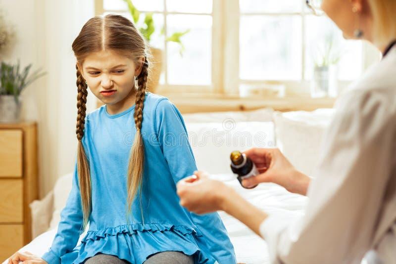 Сироп горла педиатра предлагая в ложке для девушки стоковое фото rf