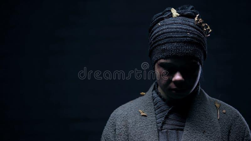 Сиротливая женская грязная ткань смотря вниз, безвыходность проблемы, социальная несправедливость стоковые фото