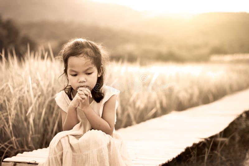 Сиротливая и унылая маленькая девочка сидя на бамбуковой дорожке стоковая фотография