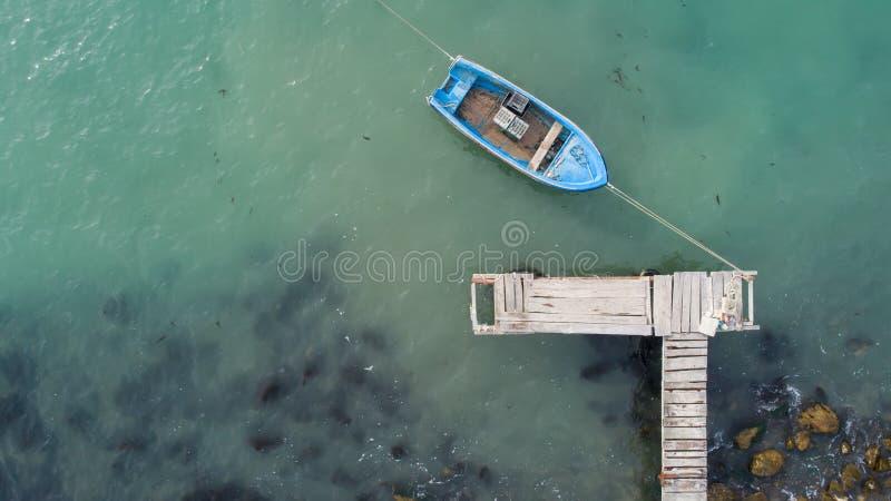 Сиротливая рыбацкая лодка и деревянная пристань в океане бирюзы, море Воздушное фото, взгляд сверху стоковое фото