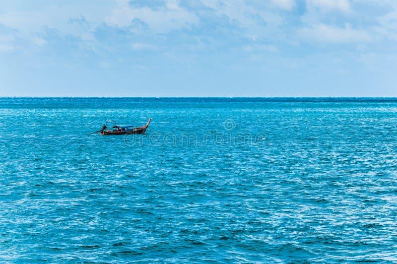 Сиротливая шлюпка в океане с голубым небом на предпосылке стоковые фото