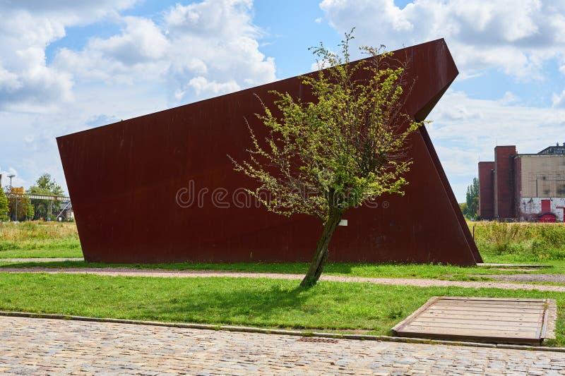 Сиротливое дерево в солнечном свете с ржавым металлом на предпосылке стоковые фото