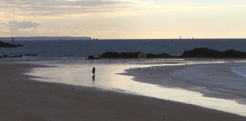 Сиротливые люди на пляже на заходе солнца в Святом-Malo стоковые изображения