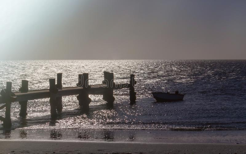 Сиротливые рыбацкая лодка и пристань моря в темном океане, море стоковые фотографии rf