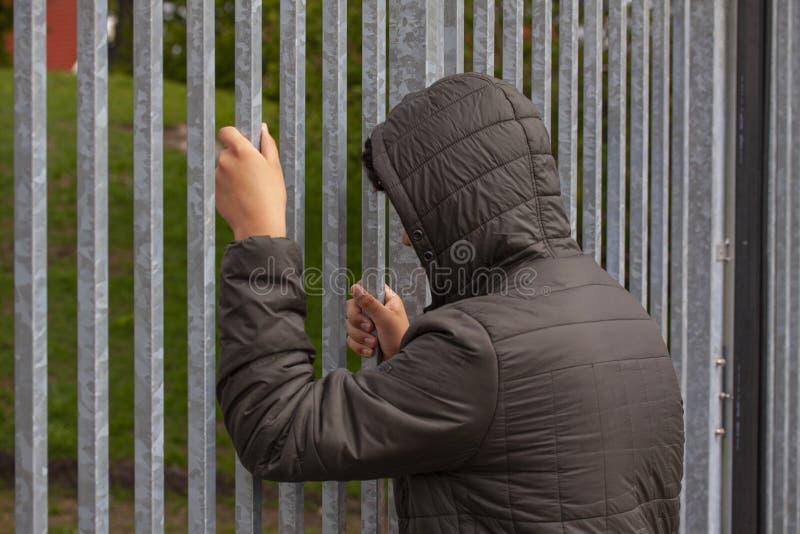 Сиротливый подросток сидя самостоятельно вне загородки металла со стальными прутами Одиночество и задирая концепция стоковое изображение