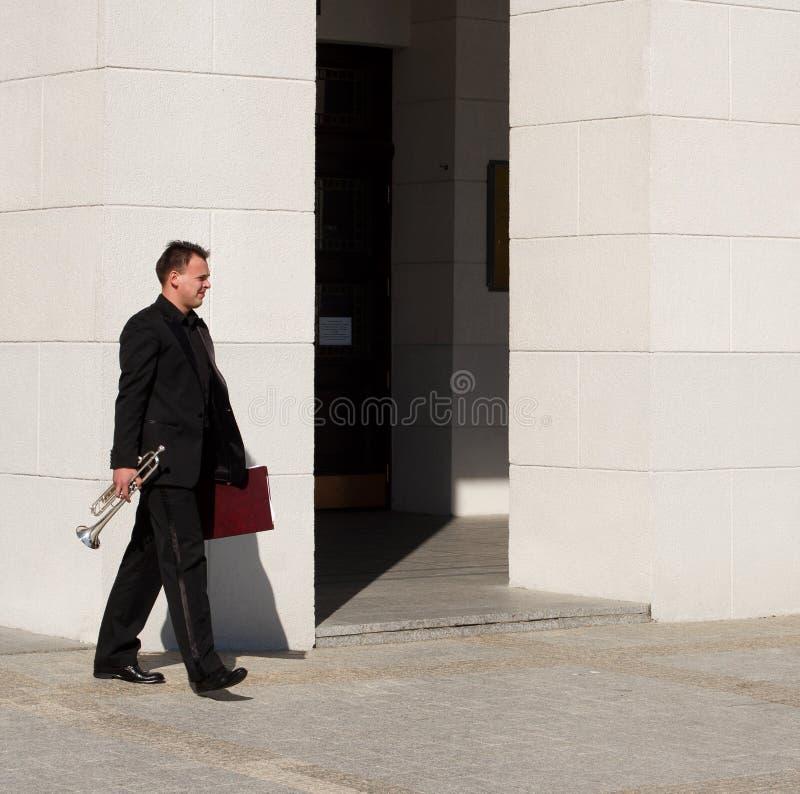 Сиротливый трубач в черном костюме с папкой с идти примечаний стоковые фото