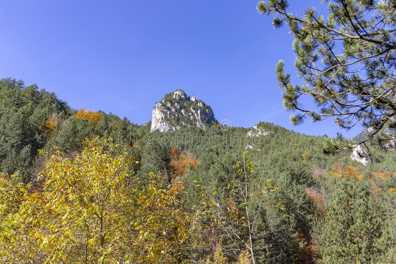 Сиротливый утес между холмами покрытыми с лесами с листвой осени стоковые фотографии rf