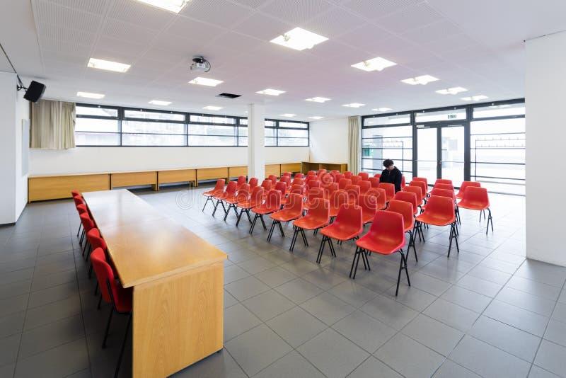 Сиротливый человек в пустом конференц-зале, концепции стоковые фотографии rf