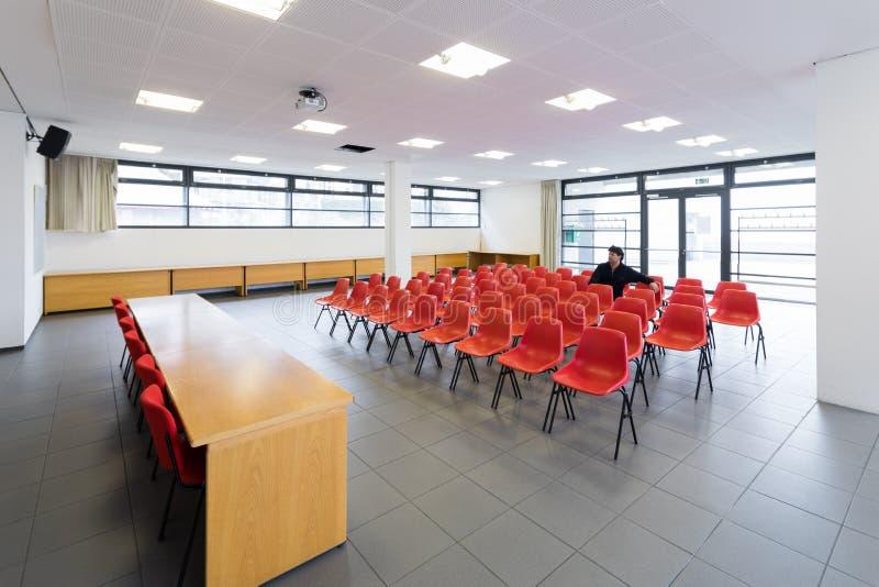 Сиротливый человек в пустом конференц-зале, концепции стоковое изображение rf