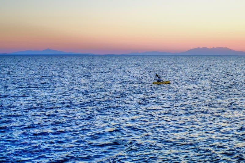 Сиротливый человек в шлюпке строки на море на заходе солнца стоковое изображение rf