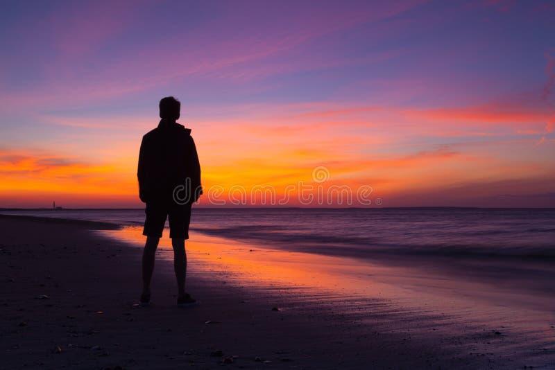 Сиротливый человек на пустом пляже на драматическом заходе солнца Треска накидки, США стоковые изображения