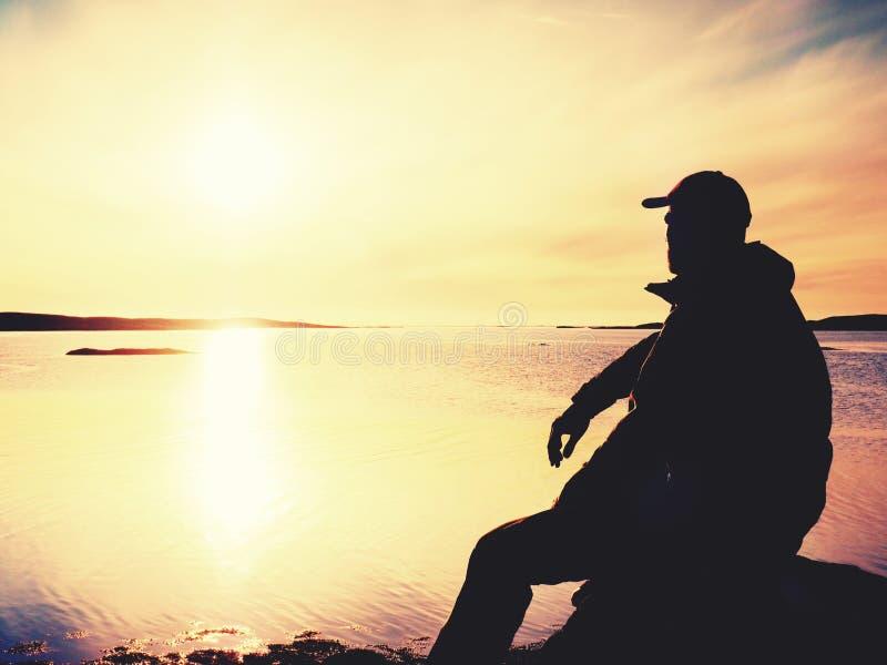 Сиротливый hiker человека сидит самостоятельно на побережье и наслаждаться заход солнца Взгляд над скалистой скалой к океану стоковое фото