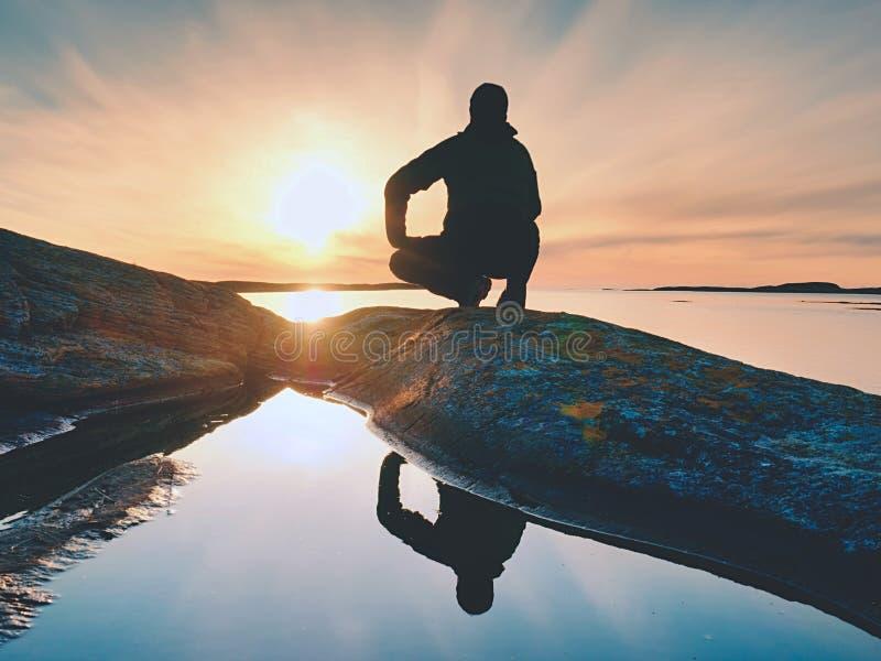 Сиротливый hiker человека сидит самостоятельно на побережье и наслаждаться заход солнца Взгляд над скалистой скалой к океану стоковые фотографии rf