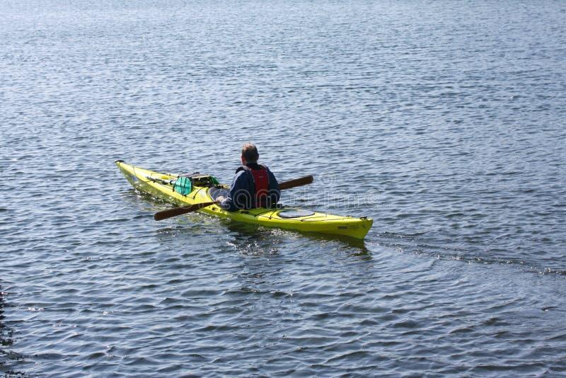 Сиротливый kayaker полоща в каяке rowing моря, активными водными видами спорта и отдыхом, сплавляться стоковое изображение