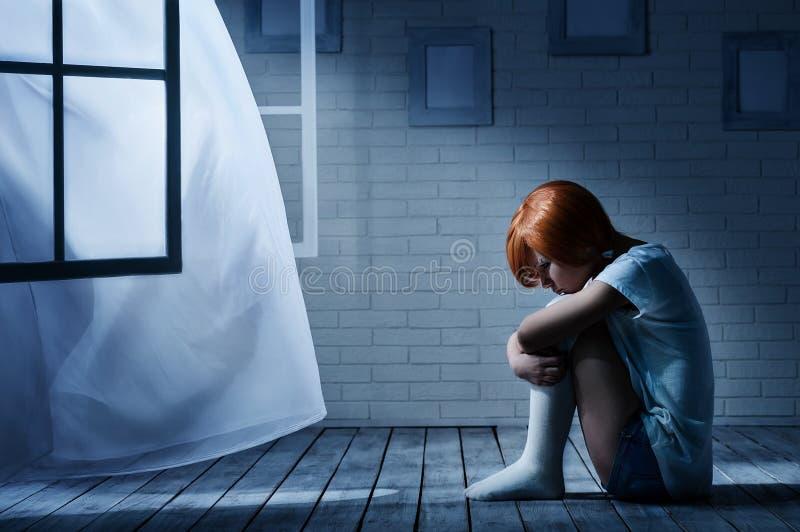 Сиротливая девушка в темной комнате стоковые изображения rf