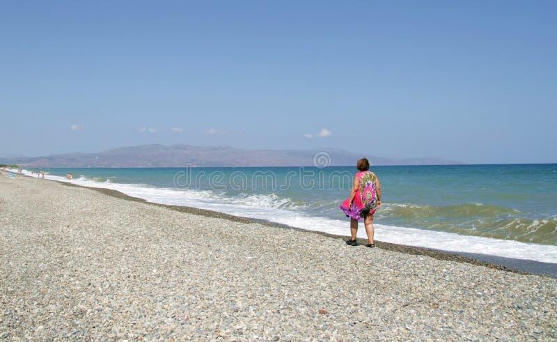 Сиротливая женщина на береге стоковое фото rf