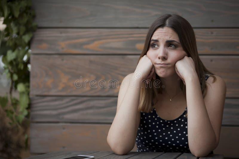 Сиротливая женщина сидя в деревянной кофейне стоковое изображение rf