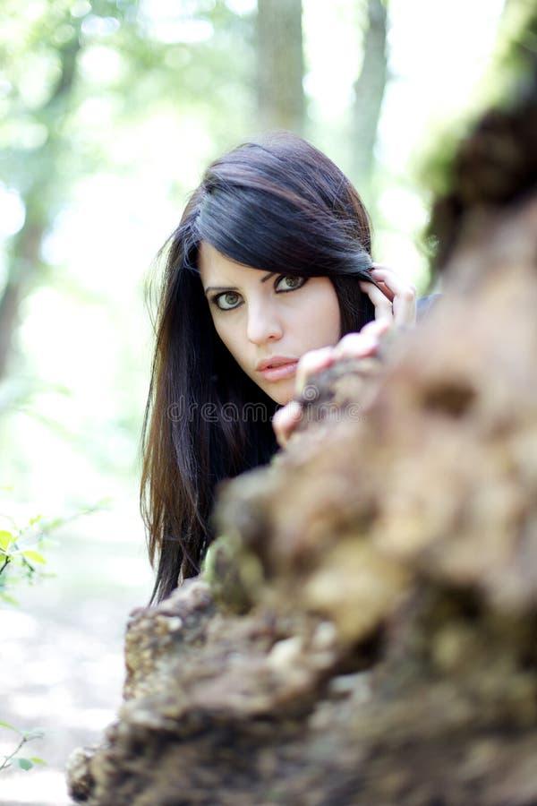Сиротливая и вспугнутая красивая женщина в древесинах стоковое изображение rf