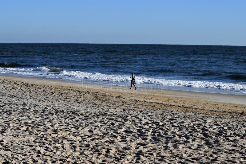 Сиротливая персона идя вдоль пляжа с прибоем стоковое изображение