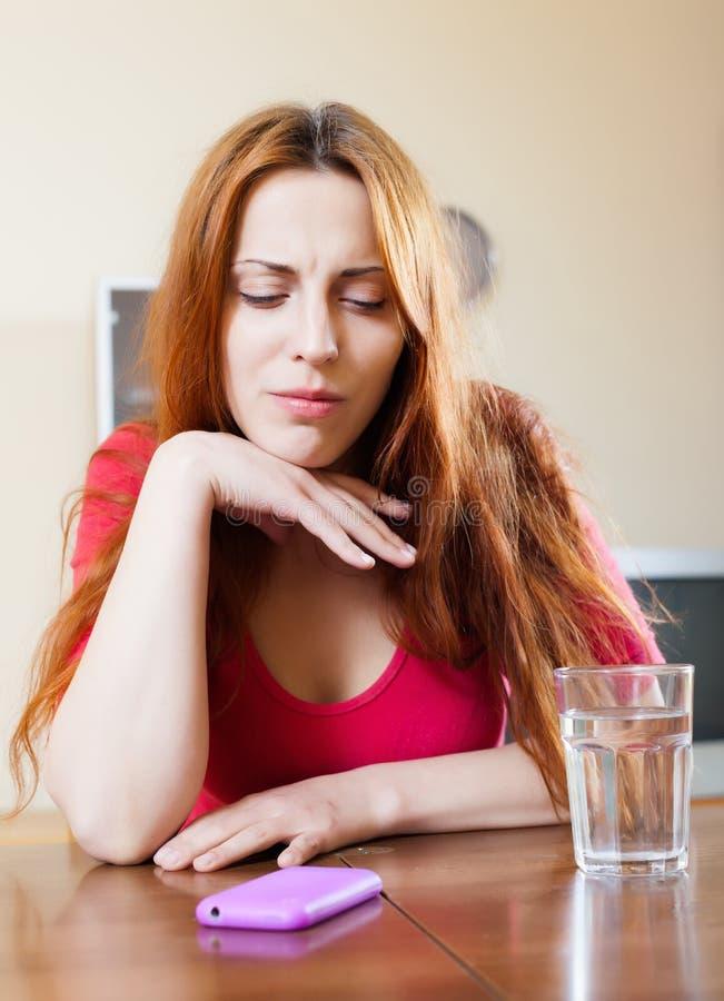 Сиротливая унылая девушка на таблице в доме стоковые фото