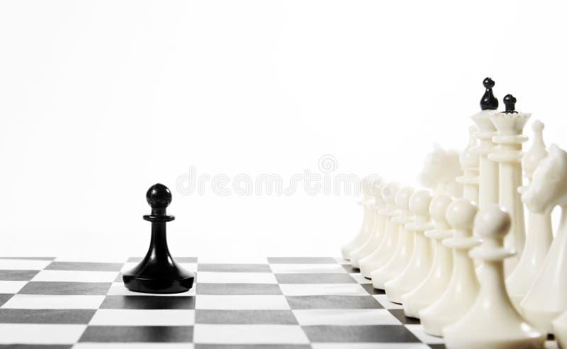 Сиротливая черная пешка перед враждебной командой Смелость и смелость стоковое фото rf
