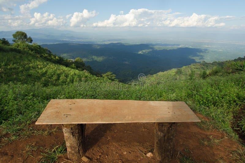 Сиротливый стул с взглядом травы, горы и облачного неба Chiangm стоковая фотография rf