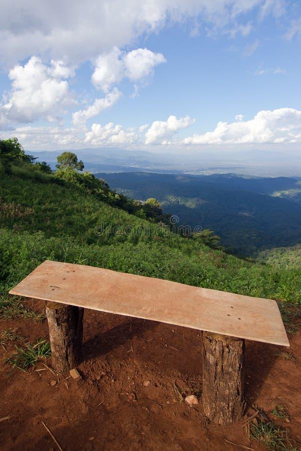 Сиротливый стул с взглядом травы, горы и облачного неба Chiangm стоковая фотография