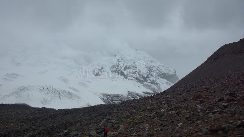 Сиротливый человек причаливая леднику вулкана Antisana на пасмурный день в запасе Antisana экологическом стоковое изображение