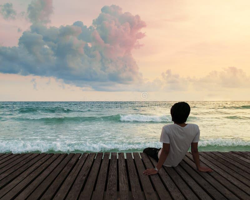 Сиротливый человек сидя в деревянной пристани дока в пляже моря с twilight небом во времени захода солнца и думает концентрат стоковые изображения