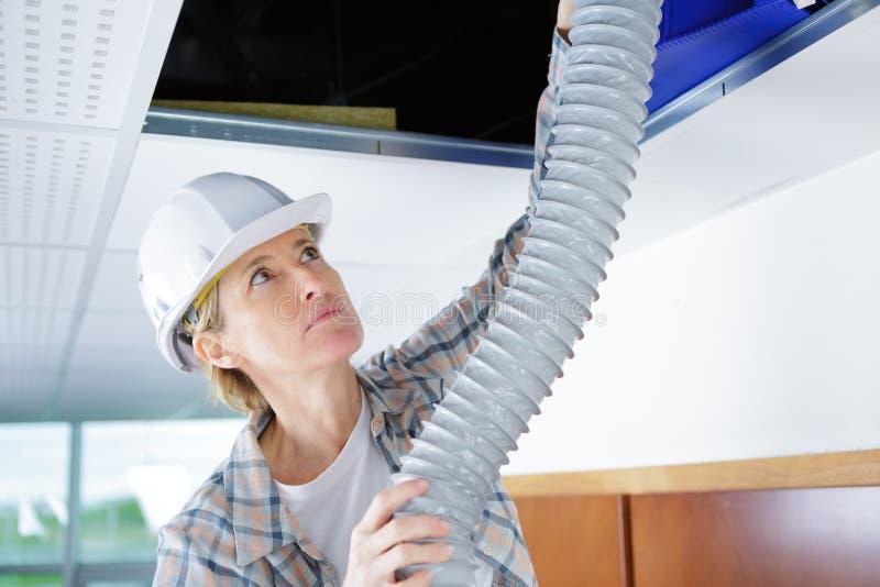 Система вентиляции женского работника подходящая в потолке зданий стоковое изображение rf
