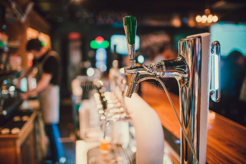 Система разливая по бутылкам пива на таблице клиентов в винзаводе стоковое изображение