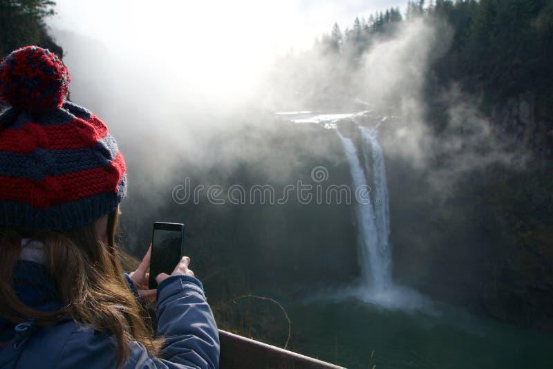СИЭТЛ, ШТАТ ВАШИНГТОН, СОЕДИНЕННЫЕ ШТАТЫ - 23-ье января 2017: дерево с туманом, сценарный взгляд падения Snoqualmie с женщиной стоковое изображение