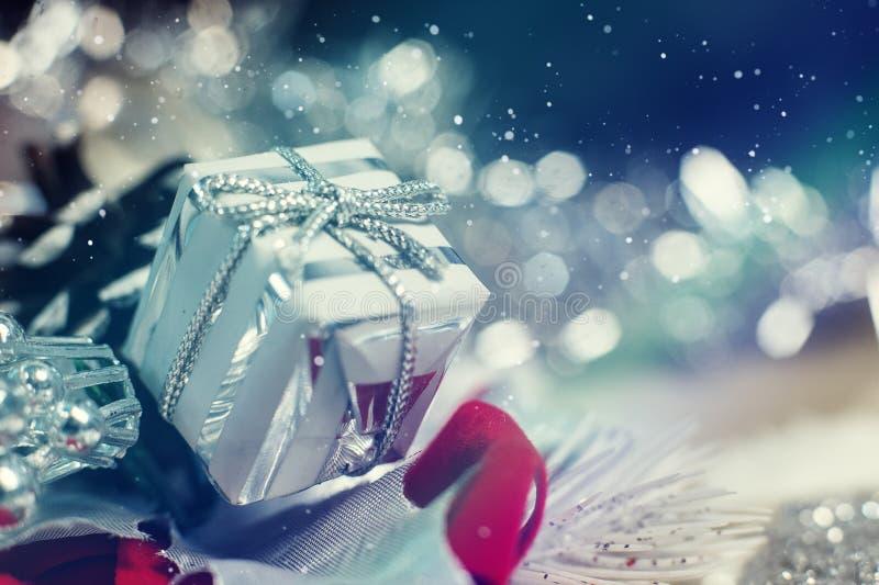Сияющая серебряная подарочная коробка рождества с падая снежинками зимы стоковое изображение