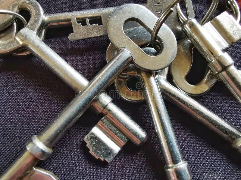 Сияющие ключи двери дома металла на черной предпосылке стоковые фото